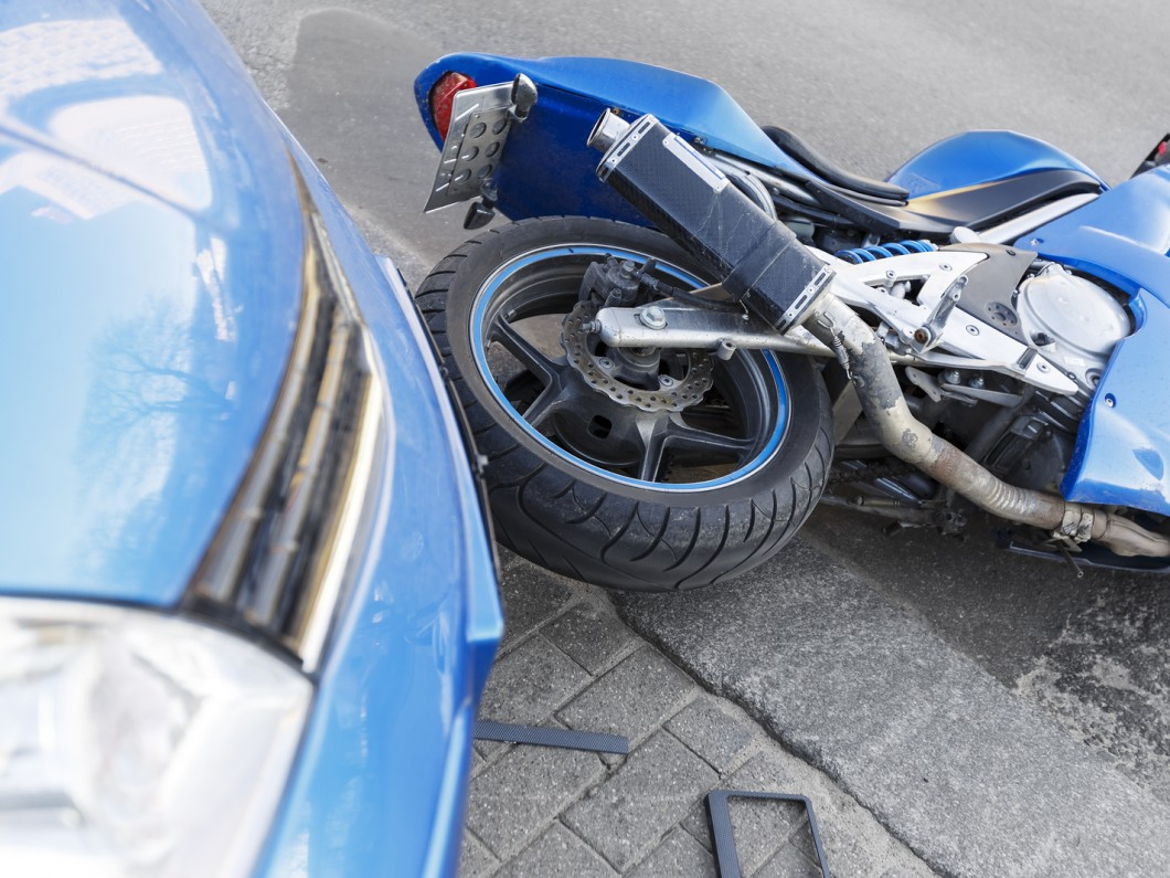 blue car and blue motorcycle toppled over