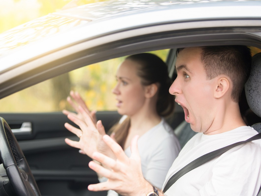 man and woman wearing white in a car and screaming