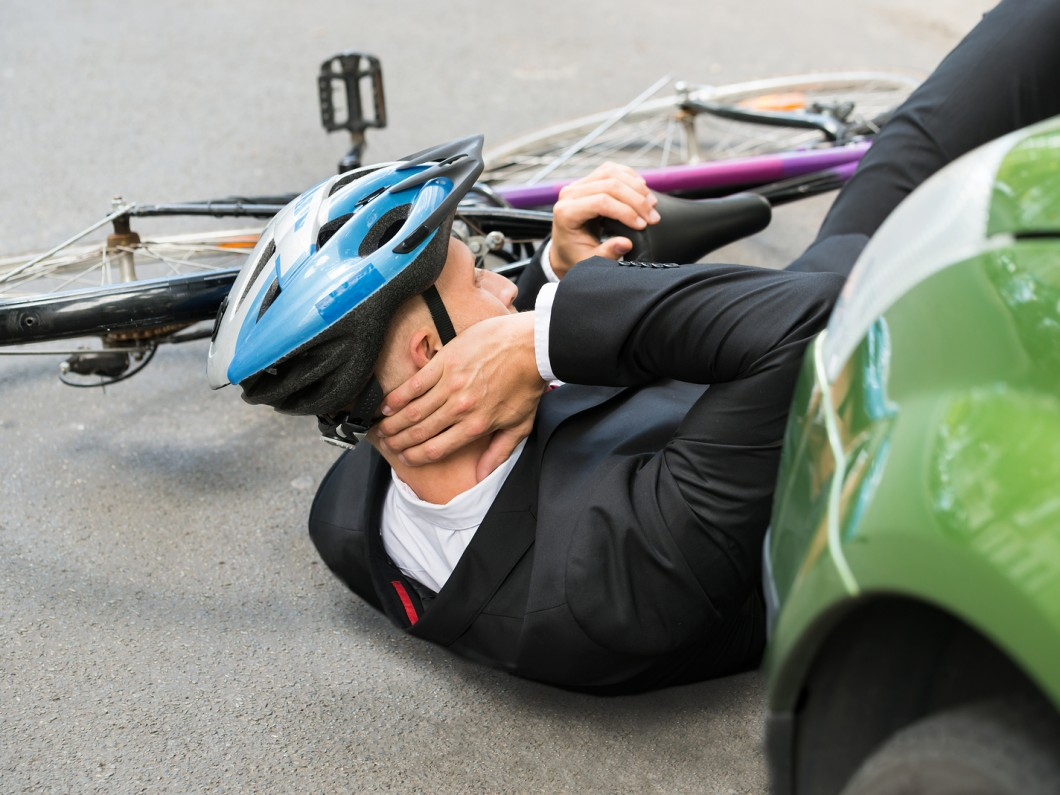 cyclist with a blue helmet holding his neck on the ground