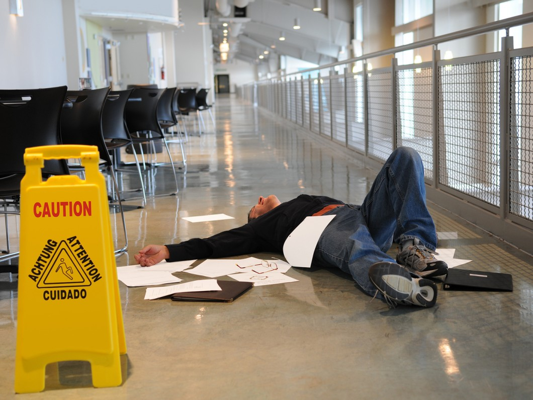 man on the ground with papers all around him next to a yellow caution sign